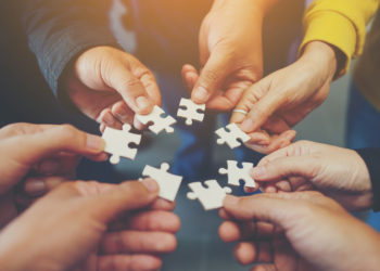hands holding jigsaw puzzle pieces